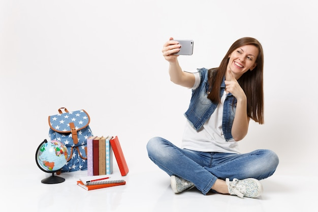 Junge glückliche studentin macht selfie-aufnahme auf dem handy, zeigt mit dem zeigefinger in der nähe von globus, rucksack, schulbücher isoliert