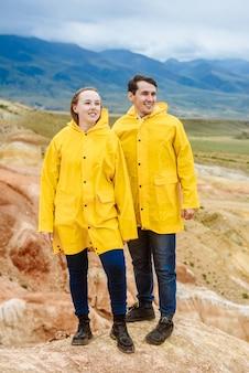 Junge glückliche touristen in gelben jacken gegen die farbigen berge des altai