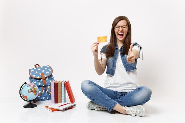 Junge glückliche überglückliche studentin mit brille blinkt mit kreditkarte und zeigt daumen nach oben in der nähe von globus rucksack schulbücher isoliert