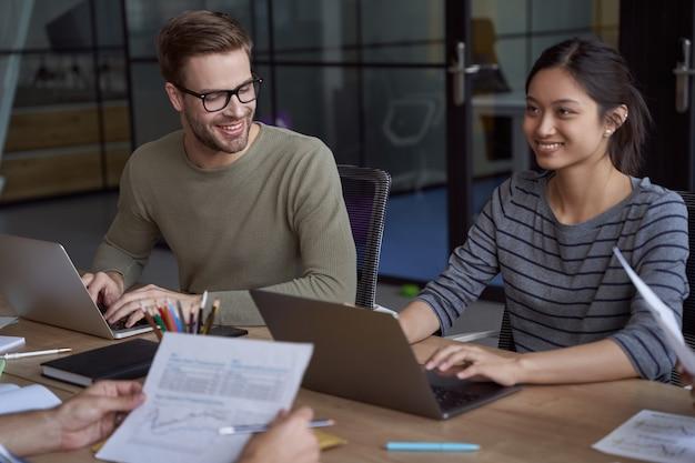Junge glückliche weibliche und männliche kollegen zusammenarbeiten, glückliche mitarbeiter, die an laptops arbeiten und