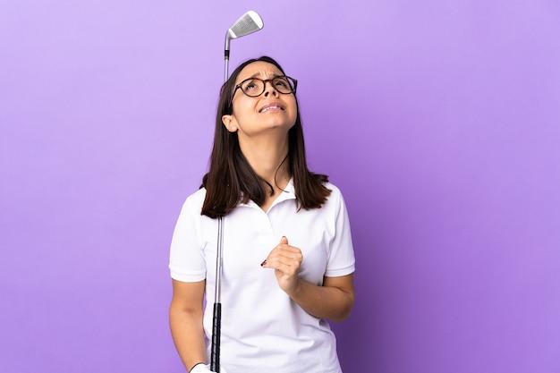 Junge golferfrau über lokalisiertem buntem hintergrund hält palme zusammen. person fragt nach etwas