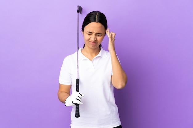 Junge golferfrau über lokalisiertem buntem hintergrund mit kopfschmerzen