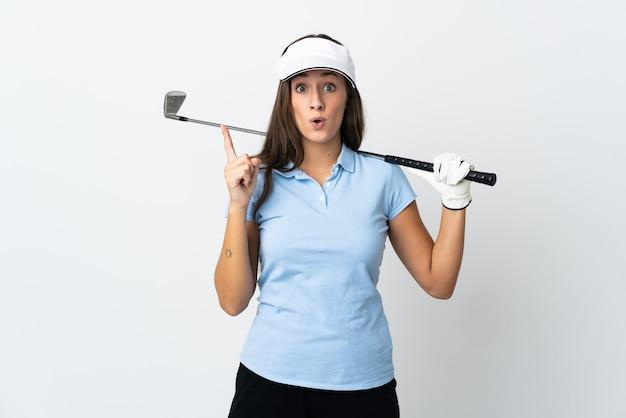Junge golferin über isoliertem weiß, das beabsichtigt, die lösung zu realisieren, während ein finger angehoben wird