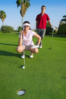 Junge golffrau, die das loch schaut und zielt