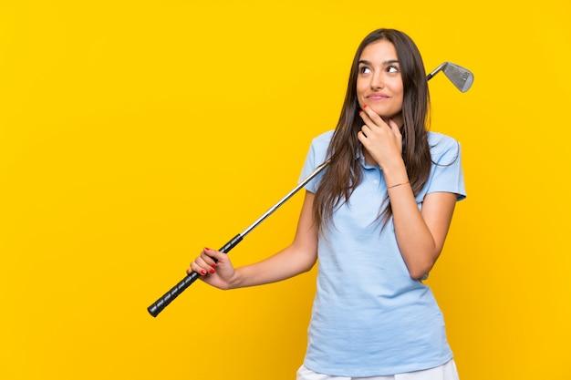 Junge golfspielerfrau über lokalisierter gelber wand eine idee denkend