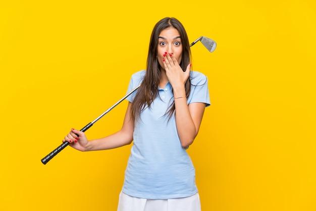 Junge golfspielerfrau über lokalisierter gelber wand mit überraschungsgesichtsausdruck