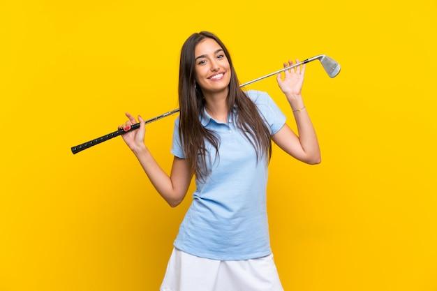 Junge golfspielerfrau über lokalisierter gelber wand