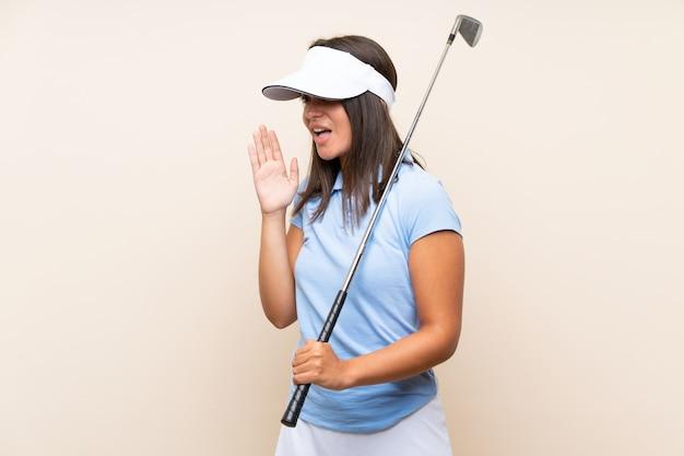 Junge golfspielerfrau über lokalisierter wand schreiend mit dem breiten mund öffnen sich