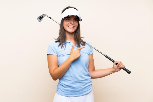 Junge golfspielerfrau über lokalisierter wand zeigend auf die seite, um ein produkt darzustellen