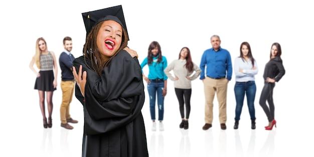 Junge graduierte die tragenden borten der schwarzen frau, die stolz und überzeugt sind und finger zeigen