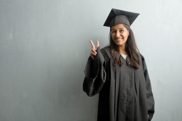 Junge graduierte indische frau gegen einen wandspaß und glücklich, positiv und natürlich und tat eine geste des sieges, friedenskonzept