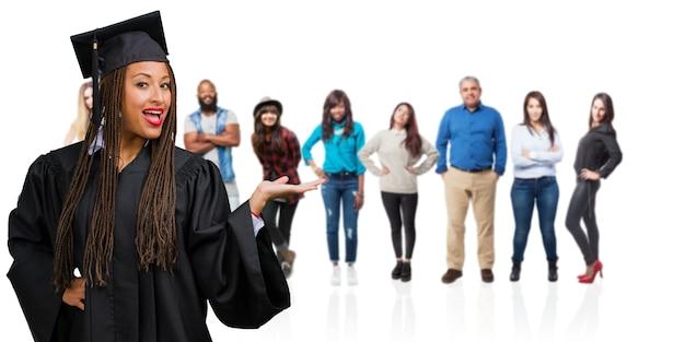 Junge graduierten die tragenden borten der schwarzen frau, die etwas mit den händen halten, ein produkt zeigen, lächeln und nett und bieten einen eingebildeten gegenstand an
