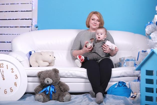 Junge großmutter mit ihrem kleinen enkel auf einem weißen sofa nahe weihnachtsbaum. blaue wand mit einem weißen mond und sternen an einer wand.