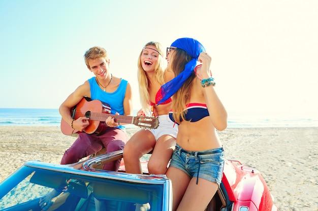 Junge gruppe, die spaß am strand spielt gitarre spielen