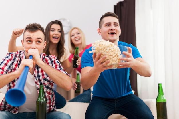 Junge gruppe von menschen, die den sieg der lieblingssportmannschaft feiern