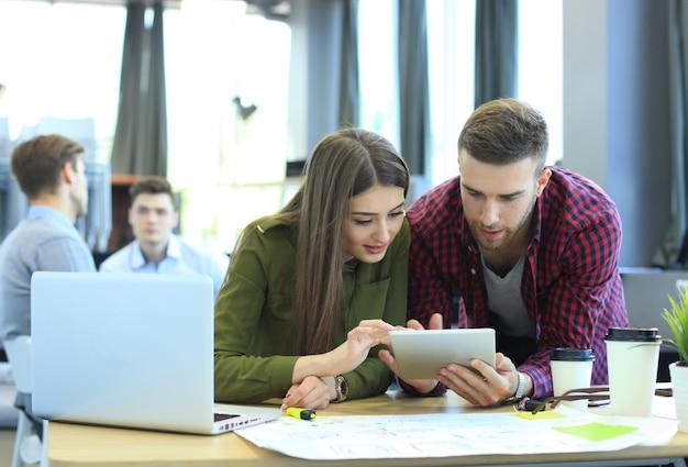 Junge gruppe von menschen, die ihre arbeit auf dem laptop erledigen.