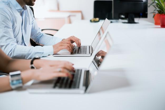 Junge gruppe von menschen, die ihre arbeit auf laptops erledigen.