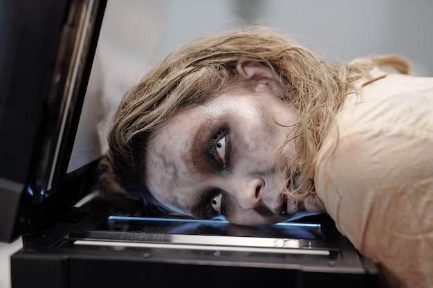 Junge gruselige geschäftsfrau mit offenen augen und zombie-schmierlack im gesicht, die ihren kopf auf dem bildschirm der xerox-maschine vor der kamera hält