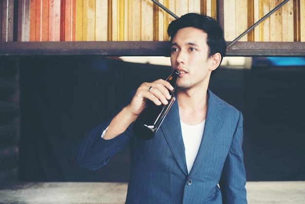Junge gut aussehend kaufmann trinken bier draußen.