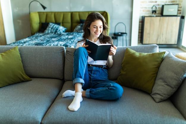 Junge gut aussehende frau, die ein buch liest, während sie auf einem sofa im wohnzimmer liegt