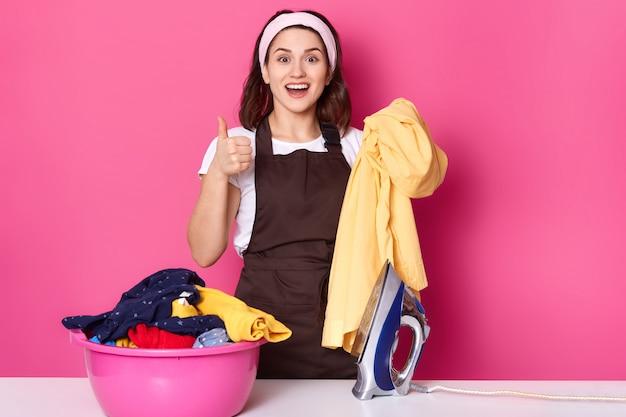 Junge gut aussehende frau steht in der nähe des schreibtisches mit frischer wäsche und bügeleisen, bereit zum bügeln, zeigen ok-zeichen