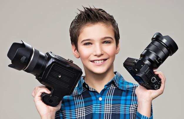 Junge hält die beiden fotokameras. lächelnder kaukasischer junge mit dslr-kamera, die im studio über grauem hintergrund aufwirft