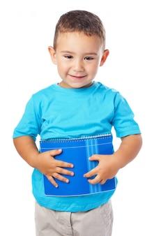 Junge hält ein notebook vor seinem bauch