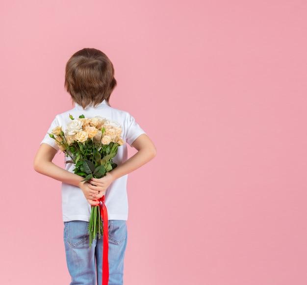 Junge hält einen blumenstrauß hinter seinem rücken auf einem rosa hintergrund. konzept von feiertagen, geburtstag, valentinstag und muttertag.