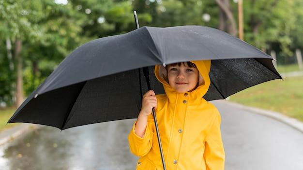 Junge hält einen geöffneten regenschirm