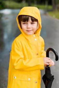 Junge hält einen geschlossenen regenschirm
