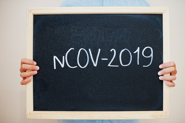 Junge hält inschrift an der tafel mit dem text ncov-2019