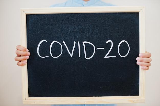 Junge hält inschrift auf der tafel mit dem text covid-20