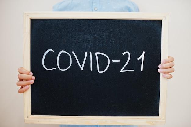 Junge hält inschrift auf der tafel mit dem text covid-21
