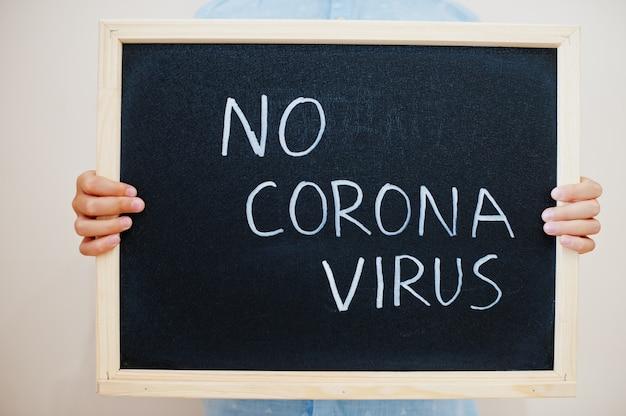 Junge hält inschrift auf der tafel mit dem text kein koronavirus