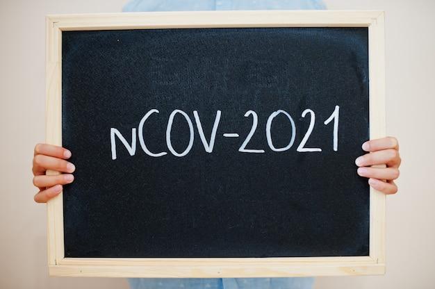Junge hält inschrift auf der tafel mit dem text ncov-2021