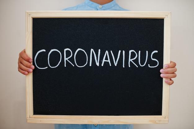 Junge hält inschrift mit coronavirus auf der tafel