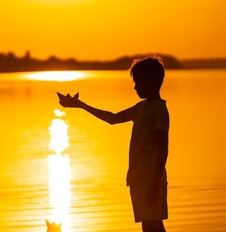 Junge hält papierschiff gegen wasser. schöner orange sonnenuntergang