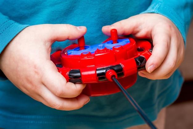 Junge hält spielzeug-bedienfeld und beherrscht moderne technologien