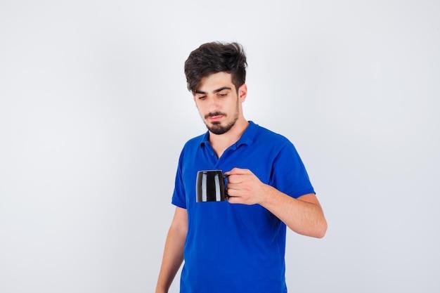 Junge hält tasse im blauen t-shirt und schaut ernst, vorderansicht.