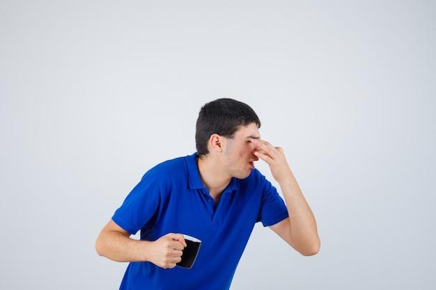 Junge hält tasse, kneift die nase wegen schlechten geruchs im blauen t-shirt und sieht gereizt aus. vorderansicht.