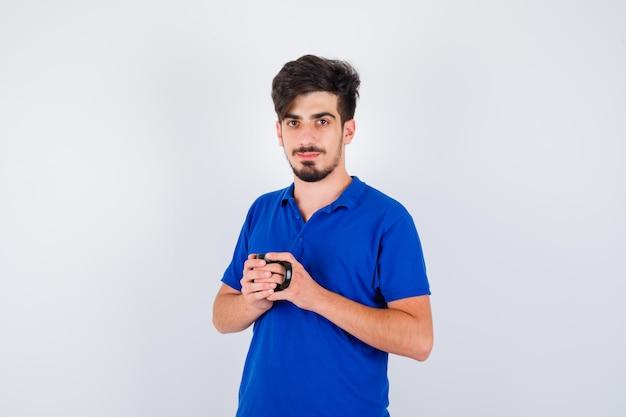 Junge hält tasse mit beiden händen im blauen t-shirt und sieht ernst aus. vorderansicht.