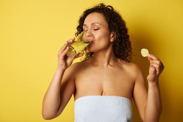 Junge halbnackte frau, eingewickelt in ein handtuch, hält eine gurkenscheibe und trinkt wasser aus einem glas