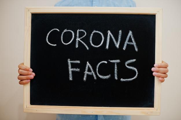 Junge halten inschrift an der tafel mit dem text corona fakten