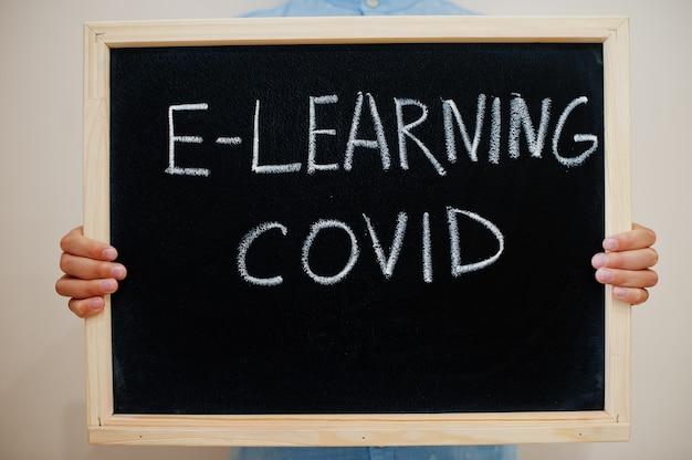 Junge halten inschrift an der tafel mit dem text e-learning covid