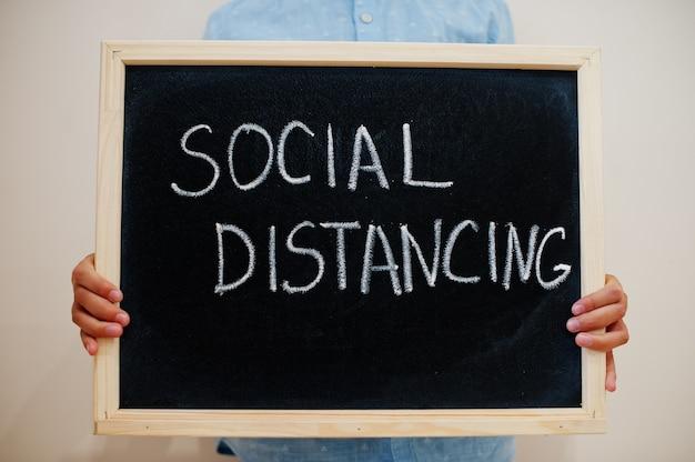 Junge halten inschrift an der tafel mit dem text soziale distanzierung Premium Fotos
