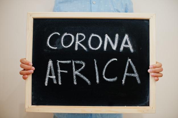 Junge halten inschrift auf der tafel mit dem text corona africa