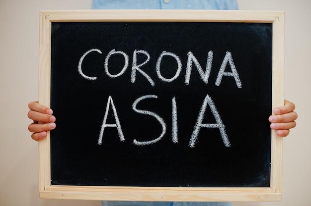 Junge halten inschrift auf der tafel mit dem text corona asia