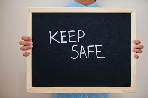Junge halten inschrift auf der tafel mit keep safe