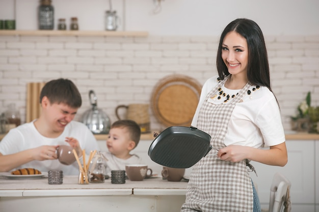 Junge hausfrau auf küchenhintergrund. frau zu hause küche. weibliches kochen mit kopierraum.