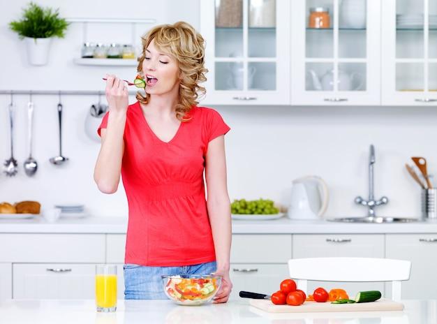 Junge hausfrau, die gemüsesalat in der küche isst - drinnen